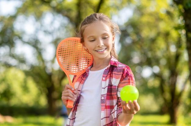 Uśmiechnięta dziewczyna z rakietą tenisową i piłką