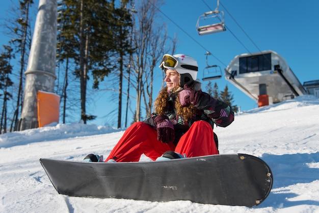 Uśmiechnięta dziewczyna z snowboardem
