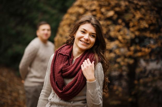 Uśmiechnięta dziewczyna z szelkami. młoda para jest ubranym na wiązanych ciepłych pulowerach ściska w miłości przy miastem w jesieni tła żółtych krzakach i drzewach.