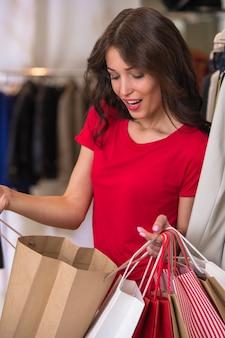 Uśmiechnięta dziewczyna z torba na zakupy przy sklepem