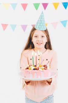 Uśmiechnięta dziewczyna z urodzinowym tortem