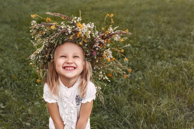 Uśmiechnięta dziewczyna z wieńcem kwiatów na głowie na tle trawy patrzy na cmera