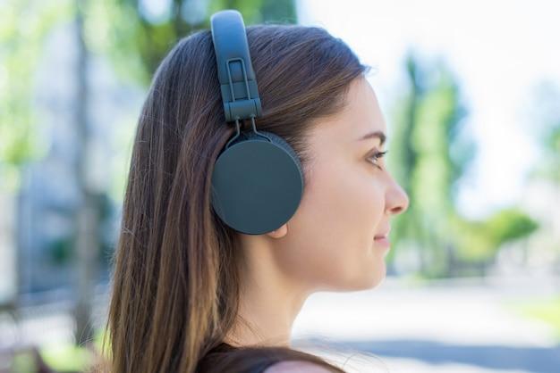 Uśmiechnięta dziewczyna za pomocą zestawu słuchawkowego