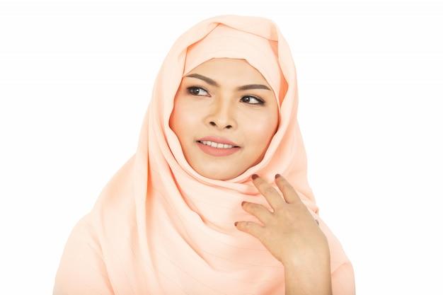 Uśmiechnięta dziewczyna zakrywa pięknego z szczęściem i koloru biel w hijab