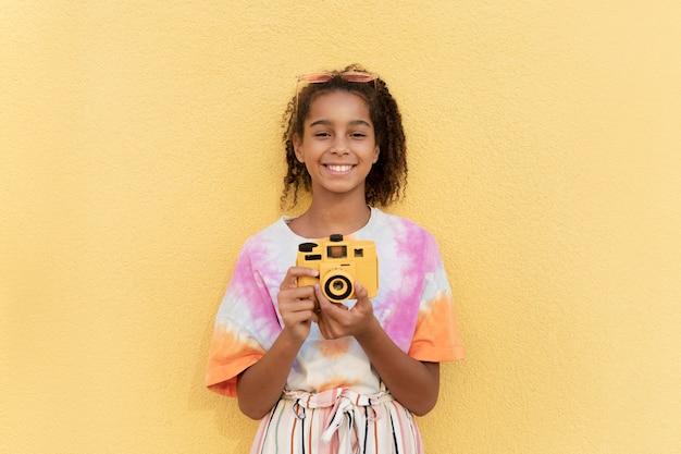Uśmiechnięta dziewczyna ze średnim strzałem trzymająca aparat fotograficzny