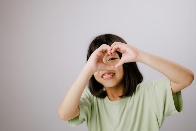 Uśmiechnięta dziewczyna ze świecącą skórą z symbolem miłości pielęgnacja oczu jest bardzo ważna