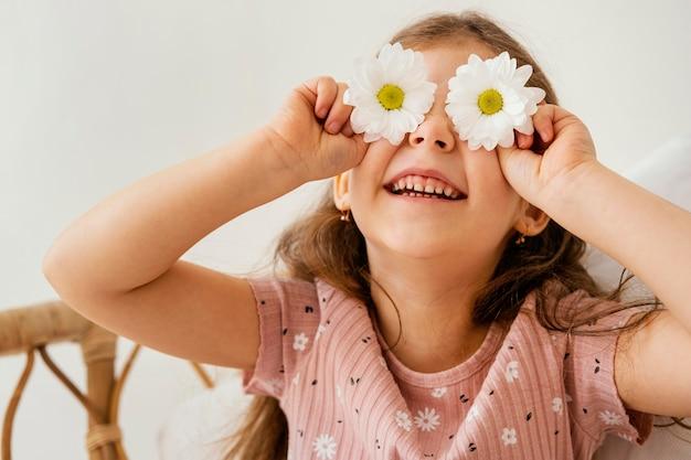 Uśmiechnięta dziewczynka bawi się wiosennymi kwiatami zasłaniającymi oczy
