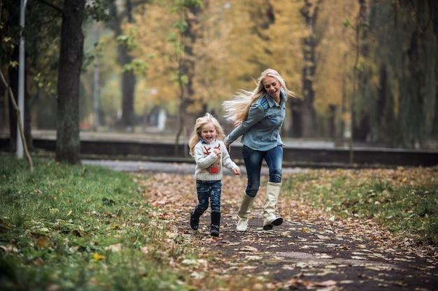 Uśmiechnięta dziewczynka bawi się z matką w parku