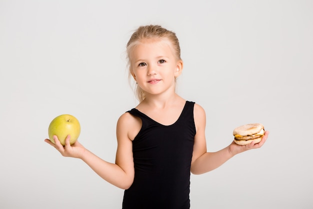 Uśmiechnięta dziewczynka dzieci trzyma jabłko i hamburger. wybór zdrowego jedzenia, bez fast foodów, miejsca na tekst