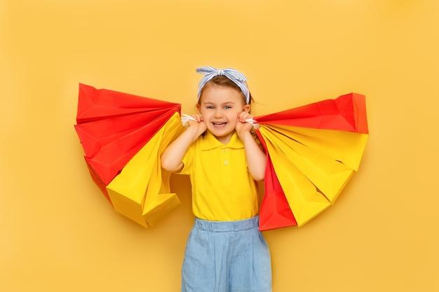 Uśmiechnięta dziewczynka dziecko trzyma paczkę torby z zakupami na białym tle na żółtej ścianie