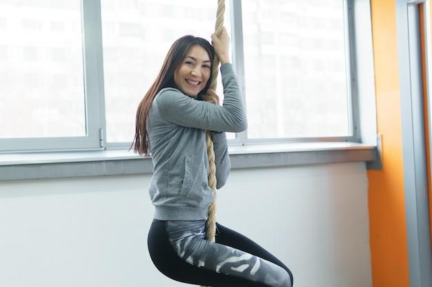 Uśmiechnięta dziewczynka fitness wspinaczka na liny w siłowni.
