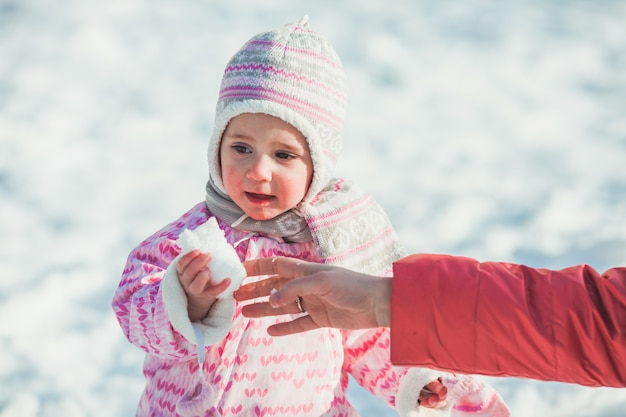 Uśmiechnięta dziewczynka po raz pierwszy w życiu chodzi po śniegu