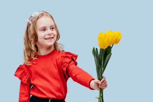 Uśmiechnięta dziewczynka pokazująca trzy żółte tulipany, ubrana na czerwono, odizolowana na niebiesko