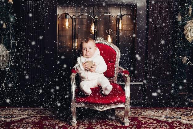 Uśmiechnięta dziewczynka poniżej 1 roku życia dekorowanie choinki w pokoju. patrząc na kamery. uroczystość. sezon wakacyjny.