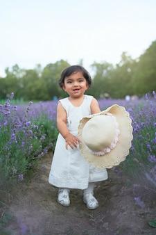 Uśmiechnięta dziewczynka pozuje na lawendowej łące