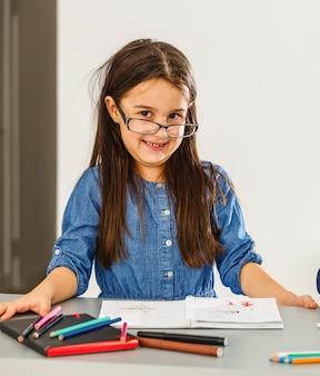 Uśmiechnięta dziewczynka przy stole, rysowanie kredkami