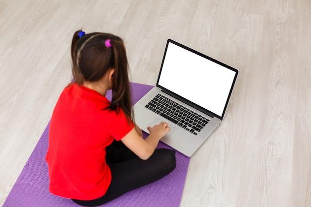 Uśmiechnięta dziewczynka robi ćwiczenia w domu