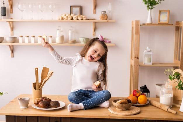 Uśmiechnięta dziewczynka siedzi na blacie kuchennym i czeka na śniadanie. wesoła i psotna dziewczyna w kuchni.