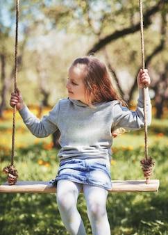 Uśmiechnięta dziewczynka siedzi na huśtawce w ogrodzie