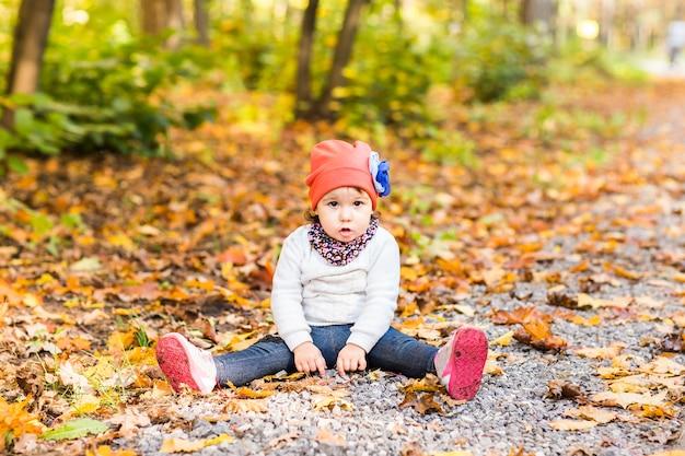 Uśmiechnięta dziewczynka siedzi na ziemi w jesiennym parku na świeżym powietrzu