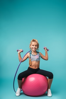 Uśmiechnięta dziewczynka sportowe robi ćwiczenia z innego sprzętu sportowego na białym tle nad niebieską ścianą