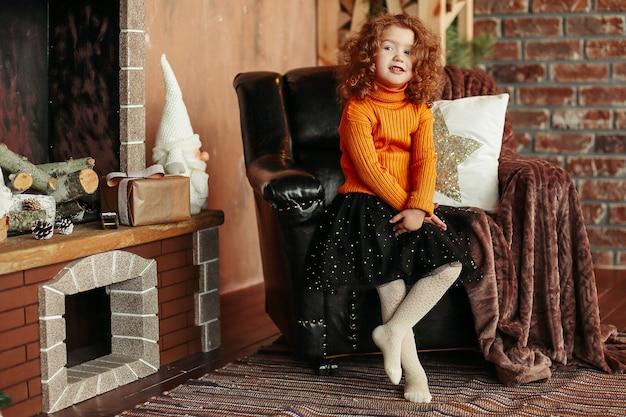 Uśmiechnięta dziewczynka stojąca przy kominku i wskazująca na ciebie. koncepcja wakacje
