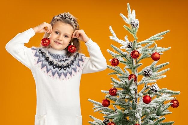 Uśmiechnięta dziewczynka stojąca w pobliżu choinki ubrana w tiarę z girlandą na szyi trzymając bombki wokół uszu na białym tle na pomarańczowym tle