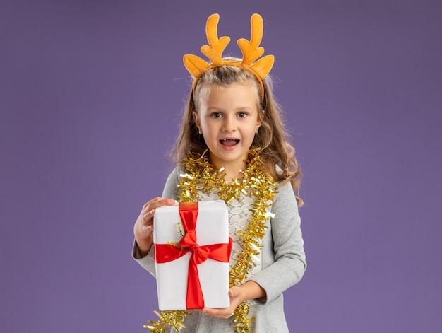 Uśmiechnięta dziewczynka ubrana w świąteczną obręcz do włosów z girlandą na szyi trzymającą pudełko na prezent na niebieskiej ścianie