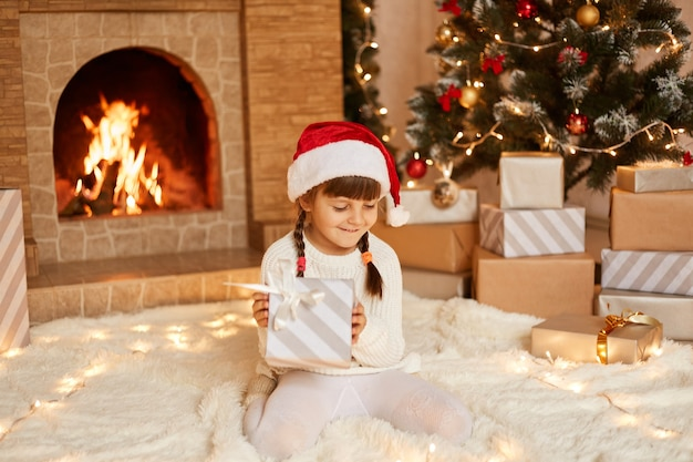 Uśmiechnięta dziewczynka w białym swetrze i czapce świętego mikołaja, siedząca na podłodze w pobliżu choinki, pudełek prezentowych i kominka, trzymająca w rękach prezent od rodziców.