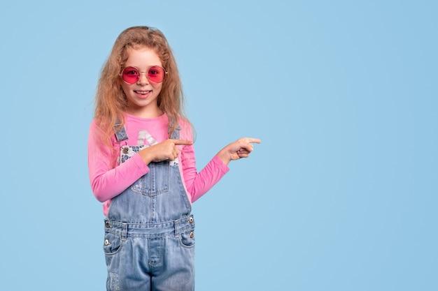 Uśmiechnięta dziewczynka w dżinsowym kombinezonie i modnych różowych okularach przeciwsłonecznych, wskazując na miejsce