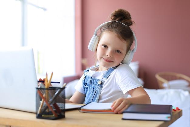 Uśmiechnięta dziewczynka w słuchawkach pismo ręczne studiować online za pomocą laptopa w domu, słodkie szczęśliwe małe dziecko w słuchawkach wziąć lekcję internetową lub klasę na komputerze.