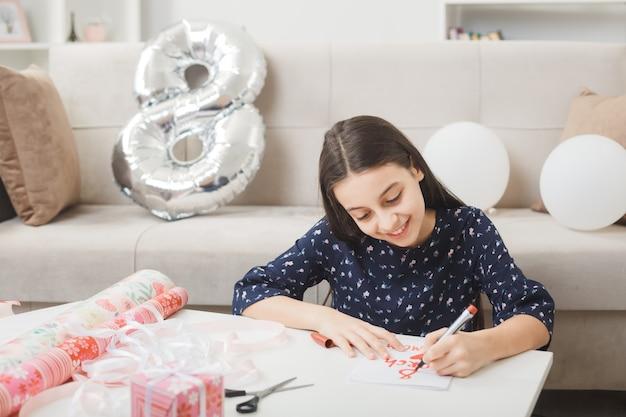 Uśmiechnięta dziewczynka w szczęśliwy dzień kobiet pisze na kartce z życzeniami, siedząc na podłodze za stolikiem kawowym z prezentami w salonie