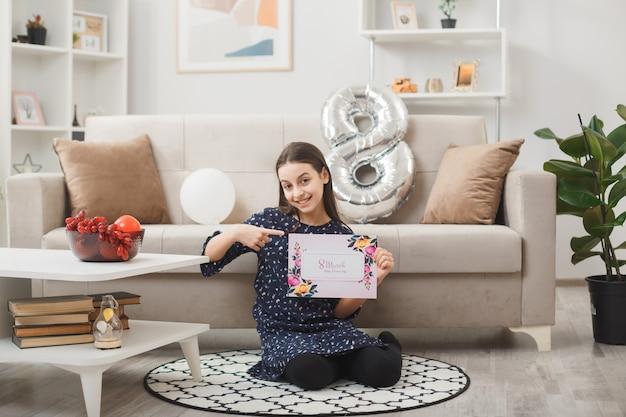 Uśmiechnięta dziewczynka w szczęśliwy dzień kobiet siedzi na podłodze trzymając i wskazuje kartkę z życzeniami w salonie