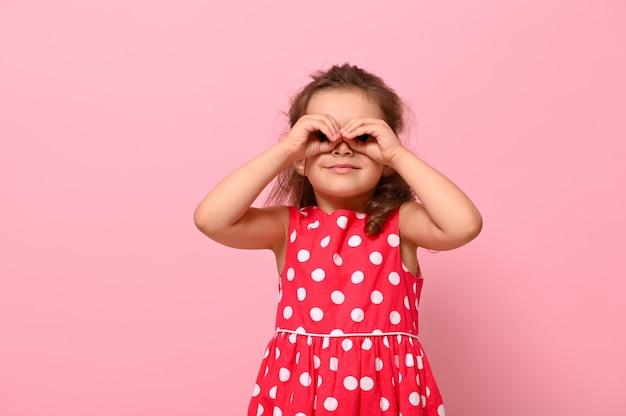 Uśmiechnięta dziewczynka w wieku przedszkolnym w różowej sukience w kropki, naśladująca dłońmi lornetkę i patrząca przez nią. urocze dziecko wyrażające pozytywne emocje pozowanie na różowym tle