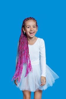 Uśmiechnięta dziewczynka z długimi różowymi włosami, ubrana w białą baletową sukienkę, na niebieskiej przestrzeni. widok pionowy.