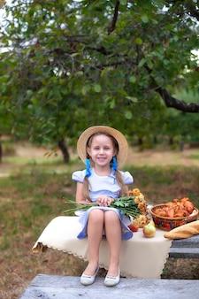 Uśmiechnięta dziewczynka z dwoma warkoczykami na głowie na pikniku w ogrodzie. letnie wakacje. skopiuj miejsce. natura, koncepcja zdrowej żywności.