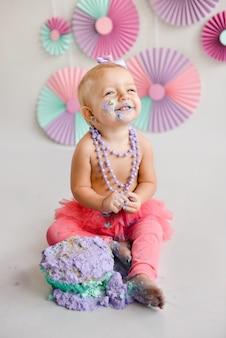 Uśmiechnięta dziewczynka z okazji urodzin została posmarowana ciastem