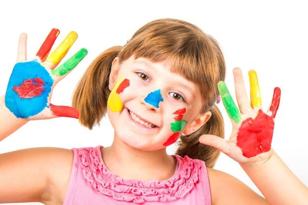 Uśmiechnięta dziewczynka z rękami malowanymi kolorowymi farbami
