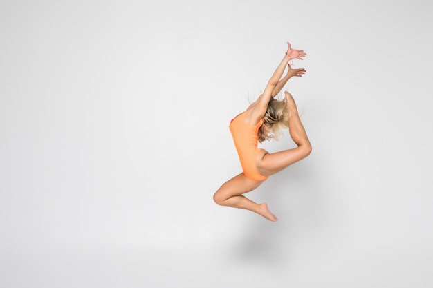 Uśmiechnięta elastyczna dziewczyny gimnastyczka w kostiumu robi rozciągania ćwiczeniu