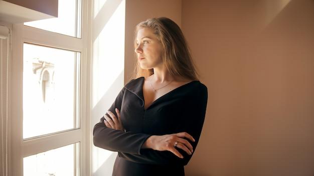 Uśmiechnięta elegancka bizneswoman patrząca przez okno o zachodzie słońca