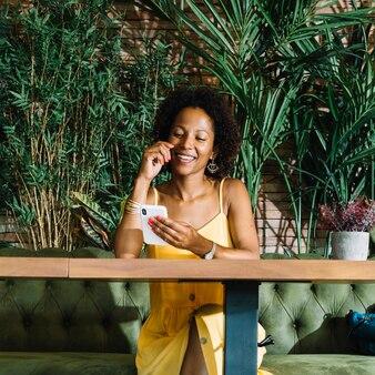 Uśmiechnięta elegancka młoda kobieta patrzeje telefon komórkowego w restauraci