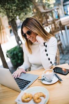 Uśmiechnięta elegancka młoda kobieta używa laptop przy stołem z napojem i croissants w ulicznej kawiarni