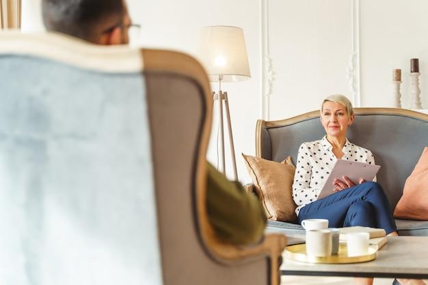 Uśmiechnięta elegancka starsza psychoterapeutka siedząca ze skrzyżowanymi nogami na kanapie przed swoim pacjentem