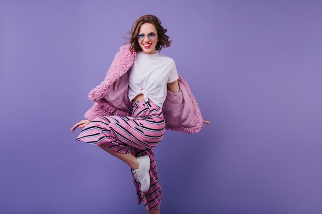 Uśmiechnięta europejska dama tańczy w futrzanej kurtce w modnych okularach przeciwsłonecznych. piękna modelka z falistymi brązowymi włosami skacząca podczas sesji zdjęciowej.