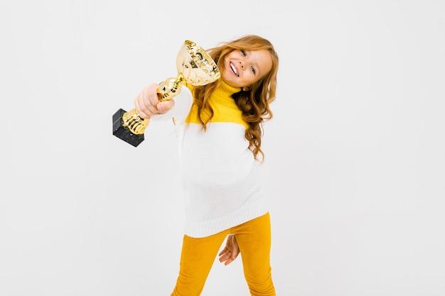 Uśmiechnięta europejska dziewczyna trzyma zwycięzca filiżankę onwhite.