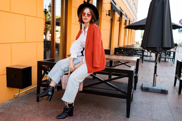 Uśmiechnięta europejska dziewczyna w słodkie pomarańczowe okulary przeciwsłoneczne, kurtka i czarny kapelusz siedzi na zewnątrz. . jesienna moda