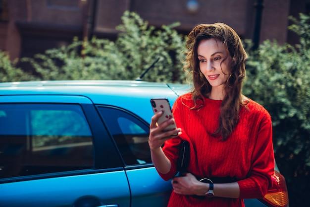 Uśmiechnięta europejska kobieta używa smartfona w pobliżu samochodu