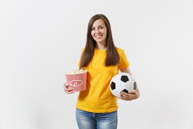 Uśmiechnięta europejska młoda kobieta, fan piłki nożnej lub gracz w żółtym mundurze, trzymając piłkę nożną, wiadro popcornu na białym tle. sport, grać w piłkę nożną, dopingować, koncepcja stylu życia fanów ludzi.