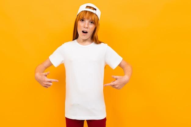 Uśmiechnięta europejska rudowłosa dziewczyna pokazuje białą koszulkę na żółto.