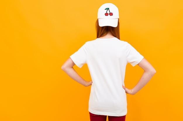 Uśmiechnięta europejska rudowłosa dziewczyna w białej koszulce stoi na plecach na żółto.